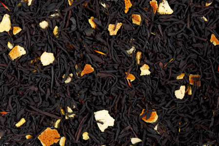 orange peel clove: Background texture of black tea with orange peels.