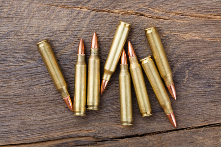 shooters: Fire arm or rifle bullet cartridges on a old wooden table.