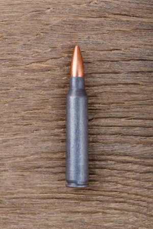ak47: Close-up photo of Ak-47 bulet on old wooden surface.