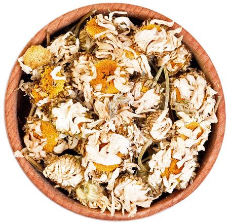 herbolaria: La manzanilla té de hierbas en un pequeño arco de madera aislado en blanco.