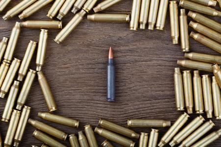 ak47: Ak-47 cartridges on wooden table close-up.