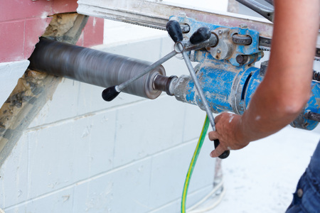 drill floor: Worker drilling holes in concrete floor at construction site.
