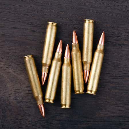 vintage rifle: Several rifle cartridges on vintage wooden surface. Stock Photo