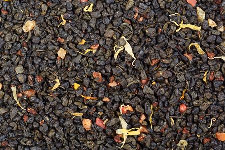 gunpowder tea: The composition of green tea (gunpowder tea) with slices of strawberry, pineapple, pomegranate and calendula flowers. Stock Photo