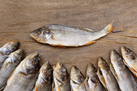 perch dried: Many dried perch on a wooden background. Stock Photo