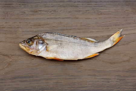 silver perch: Dried perch on a wooden background.