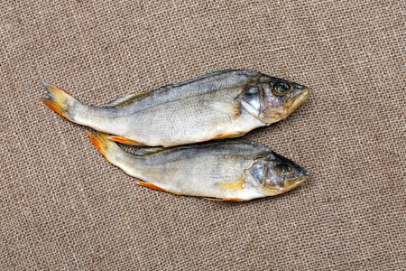 silver perch: Two dried fish on the  burlap close-up. Stock Photo