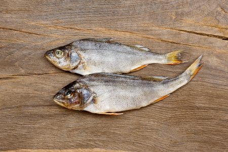 silver perch: Two dried fishes on a wooden table.