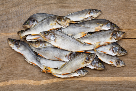 perch dried: Many dried perch on a vintage wooden background.