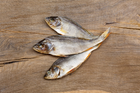silver perch: Three dried fishes on wooden background.