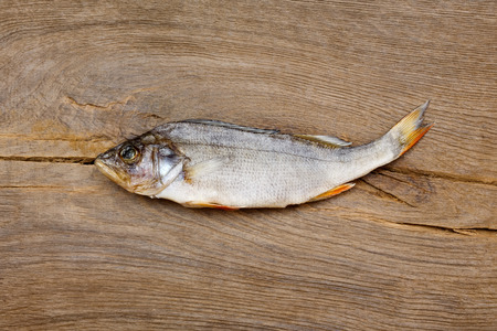 silver perch: Dried fish on the table. Salty dry river fish on a wooden impressive background.