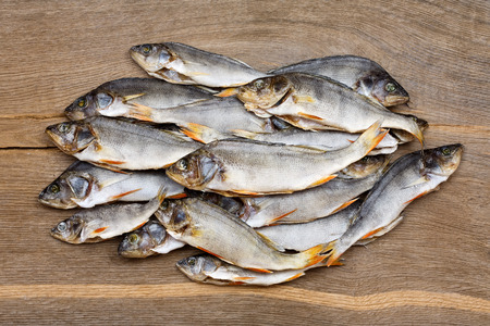 perch dried: Many dried perch on a vintage wooden table. Stock Photo