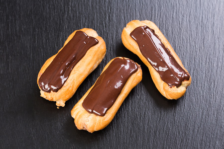 Close up of freshly baked chocolate eclairs on black background.
