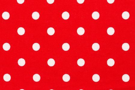 Close up of red background with white polka dots pattern.