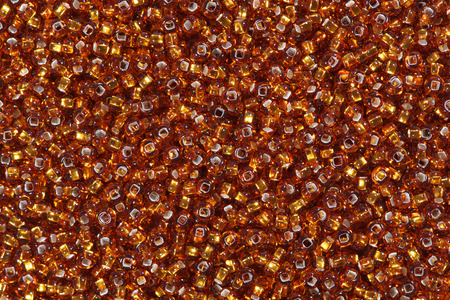 sandy brown: Close up of orange red seed beads