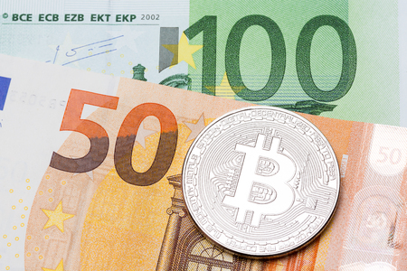 silver coins: Silver bitcoin on hundred and fifty euro background. High resolution photo.