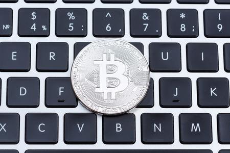 silver coins: Silver bitcoin on computer key board. High resolution photo.
