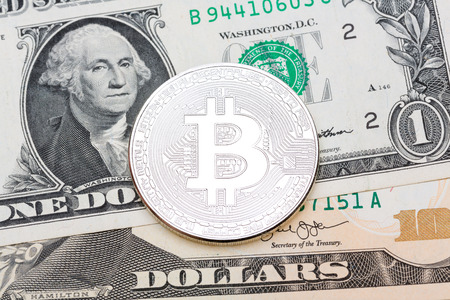 silver coins: Silver bitcoin on different dollars background. High resolution photo. Stock Photo