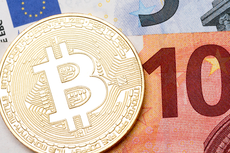 Close up of golden bitcoins on euro currency background, macro shot. High resolution photo.