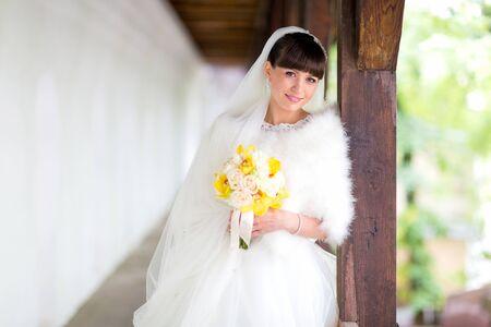 Bride in stylish wedding dress and unusual bouquet of flowers in yellow tone. 版權商用圖片