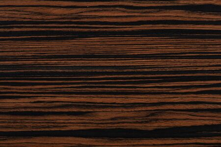 Expensive brown ebony veneer background for your unusual design project. High quality wood texture.