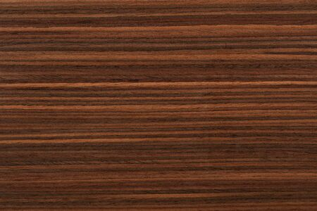 Elegant natural rosewood veneer background in brown color. High quality texture.