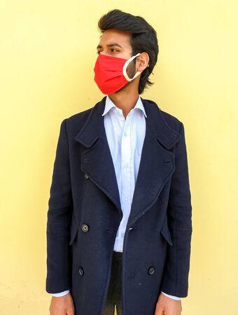 Studio shot of a young India smart man wearing coronavirus mask to protect from the coronavirus