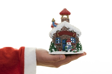 Christmas house on Santa Claus hands. photo
