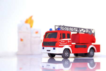 Toy fire brigade in front of burning house