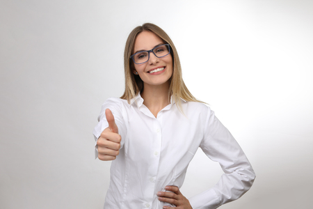 Pretty blond woman wearing glasses shows thumbs up