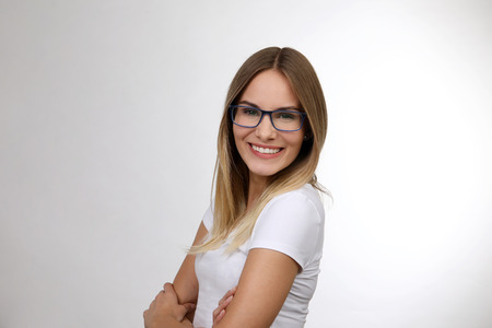 Pretty blond woman with arms crossed smiles