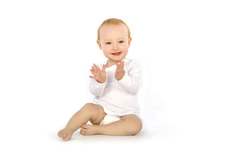 Joli bébé en chemise blanche tape dans ses mains