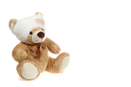 Cute teddy bear with head injury sits