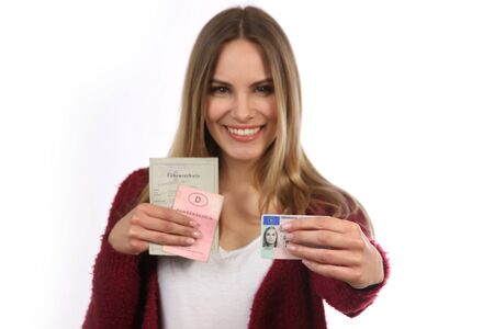 Blonde girl shows her new driving license in front of older documents