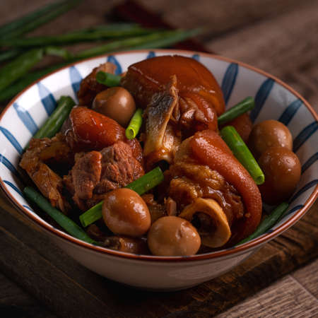 Close up of Taiwanese traditional food pork knuckle in a bowl on rustic table background.