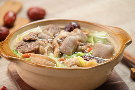 Fresh delicious mutton hot pot with vegetables and Chinese herbal medicine like goji berry and Chinese angelica Dong Quai. Foto de archivo