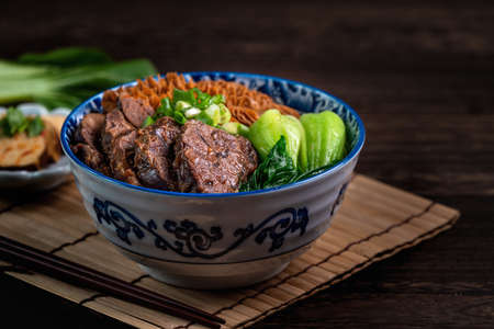 Taiwanese famous food beef noodle soup with sliced braised beef shank, tripe and vegetables on wooden table background.