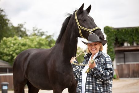 Senior Woman showing off her horse  photo
