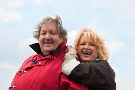 Senior couple laughing outside isolated on white photo
