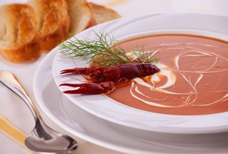 A bowl of Fish cream soup, garnished with crayfish and with a side of roasted Baguette Bread