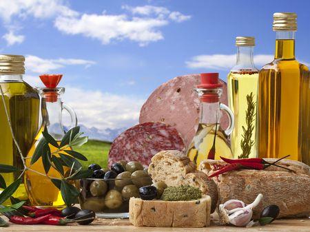 Dekorative italienischen Deli mit 5 verschiedenen Olivenöl, italienischer Brot, italienischer Baloney und Salami, Olive und Zutat auf Hintergrund Landschaft.