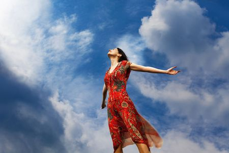 Pretty young woman with arms raised standing almost weightlessly towards the sun