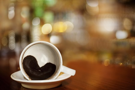 cup of coffee with Heart of Coffee Grounds on Bar, full Frame photo