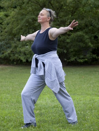 Senior woman doing Tai Chi against Outdoors Standard-Bild
