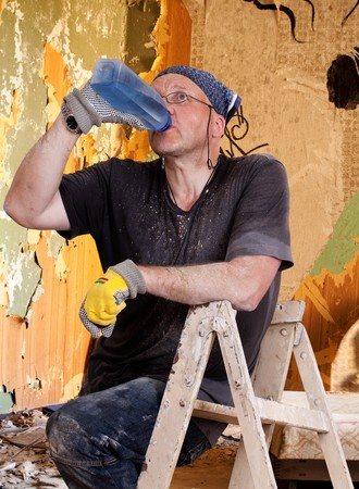 peintre en b�timent: House Painter sitting of the ladder and drinking water