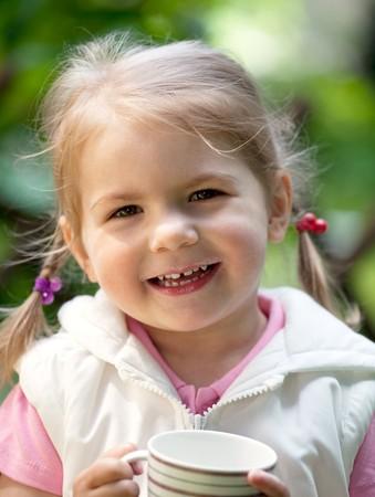 Kleines Mädchen mit Milch Tasse und haben Milch Schnurrbart Standing outdoor  Lizenzfreie Bilder