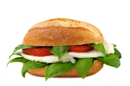 An italian sandwich with fresh buffalo mozzarella, red ripe tomatoes and basil isolated on white