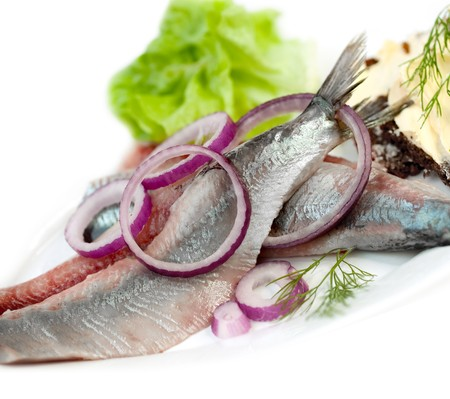 kipper: Portion of typical Dutch herring on the plate and on white Background Stock Photo