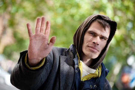 molest: Homeless Men with hand outstretched, warding off any unwelcome situations.  Stock Photo