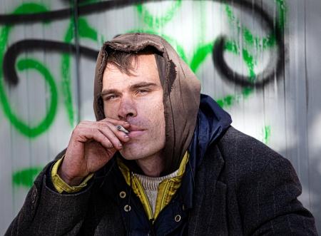 hombre sucio: Sin hogar hombres Being Friendly fuma un cigarrillo al aire libre Foto de archivo